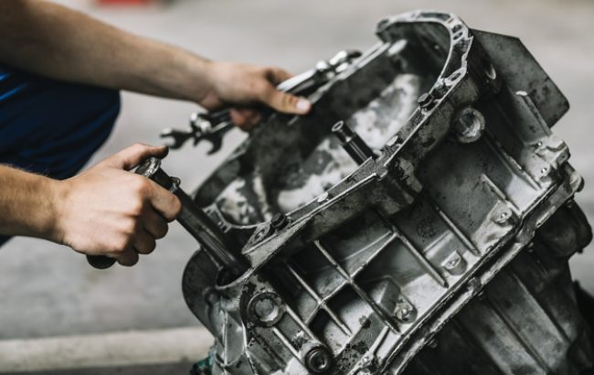 repairmen-with-wrenches-fixing-car-engine_23-2147898004